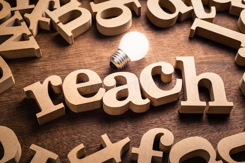 Reach Idea Topic. Reach word in scattered wood letters with glowing white light bulb royalty free stock photography