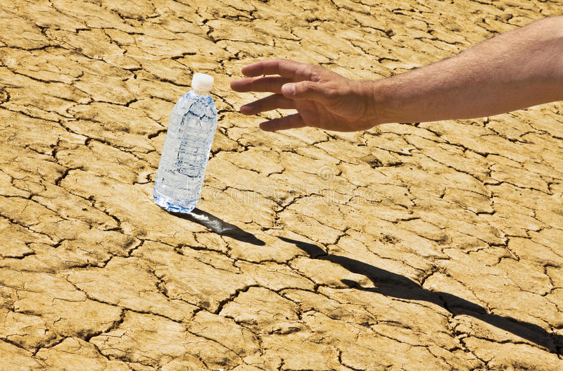 Reaching For Desert Bottled Water Tilted. A man's hand and arm is reaching in from the right side down to a bottle of water sitting on a desert playa. The royalty free stock photos
