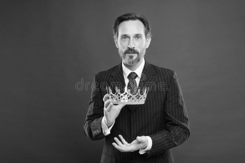 Reaching the height of luxury and elegance. Mature man holding luxury crown jewel on red background. Successful. Businessman with luxury and classy look. Luxury stock photo