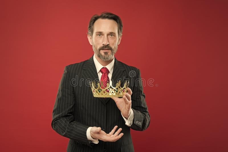 Reaching the height of luxury and elegance. Mature man holding luxury crown jewel on red background. Successful royalty free stock photos