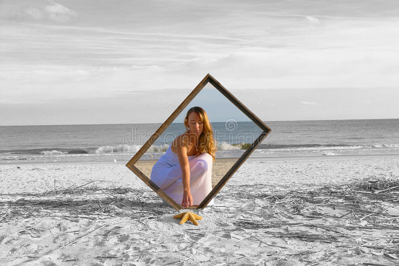 Reaching Out. Girl in a white dress on a beach reaching outside of colored picture frame to pull in a starfish from a black and white world stock images