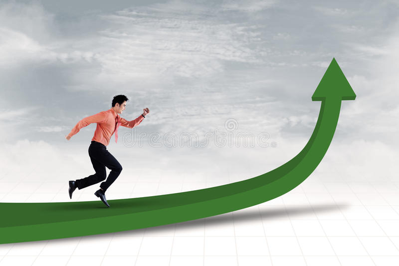 Reaching profit target. Businessman is running on line chart to achieve profit stock photography
