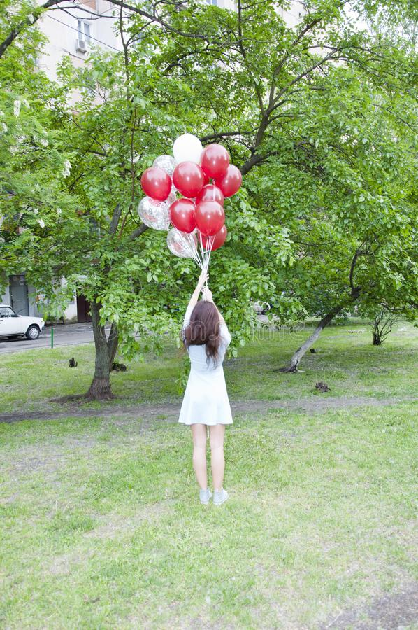 Reaching the sky. Full length shot of playful young woman holding balloons on natural green background. Reaching the sky. Full length shot of playful young royalty free stock photo