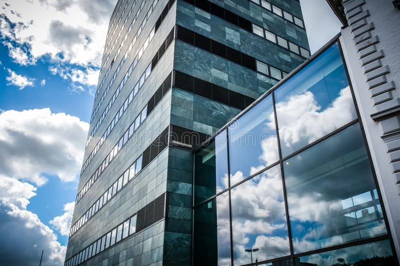 Reaching the sky - Odense, Denmark. A modern skyscraper in Odense, Denmark reflects the blue sky and white clouds - a glass box on the side almost seems to royalty free stock image
