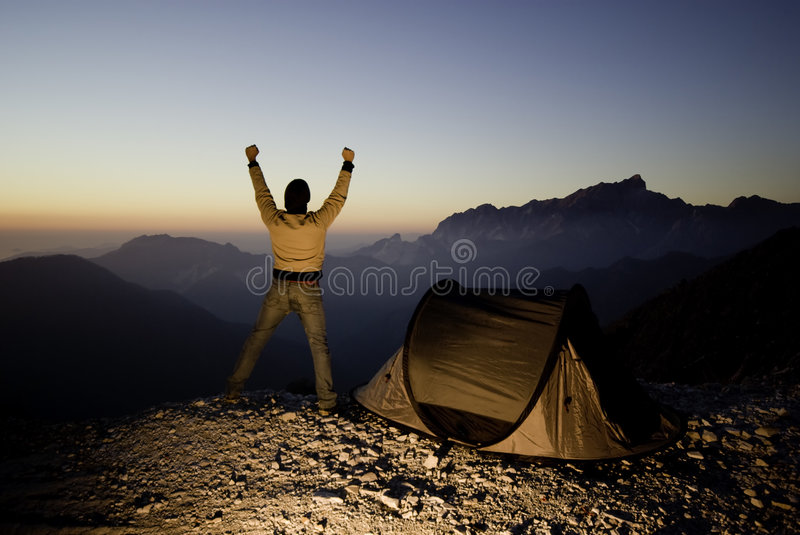 Reaching the top!. An happy hiker reachs the top of a mountain at sunset.Silhouetted style royalty free stock image