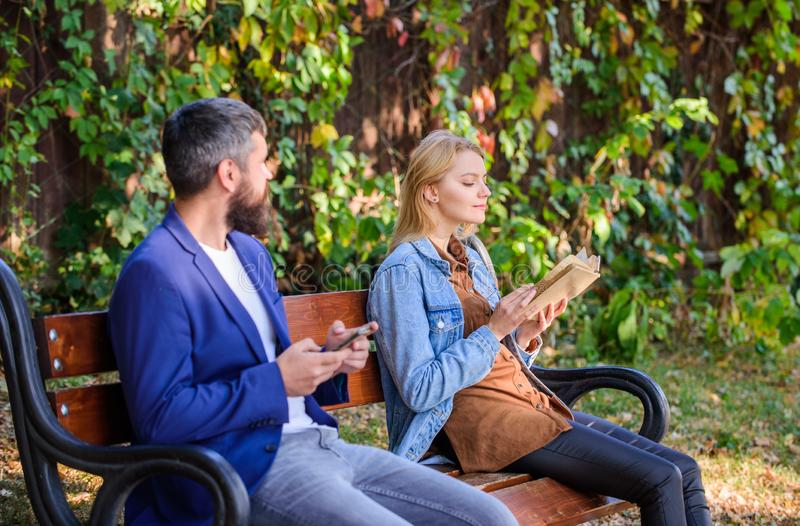 Read book in park pleasant leisure. Interesting literature. Reading hobby concept. Woman read book while man read ebook royalty free stock photo