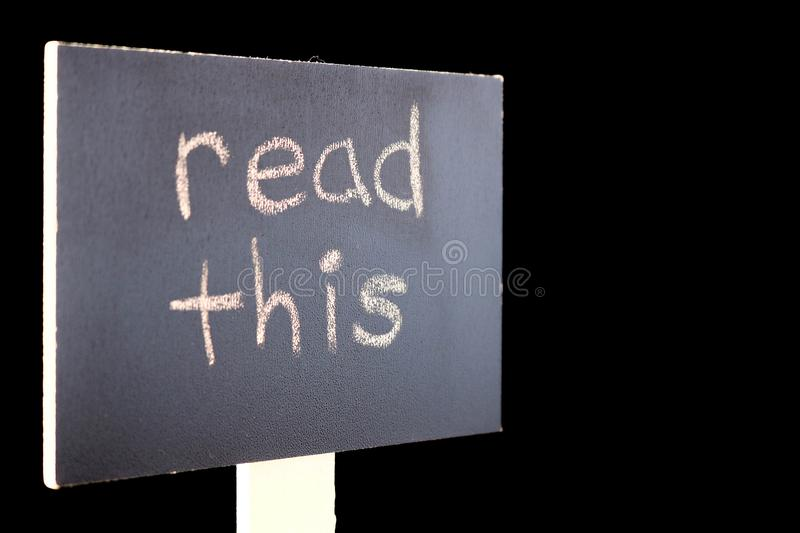 Read this - chalkboard sign. Chalkboard or blackboard sign with `read this` text - good for social media posts, blogs, internet publishing royalty free stock image