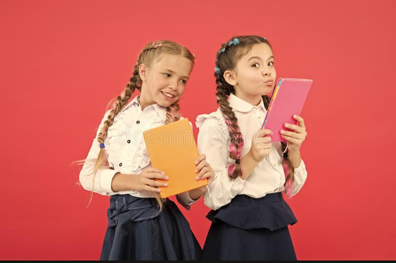 Read every day. Cute small children holding books to read on red background. Adorable little girls learning to read at royalty free stock photo