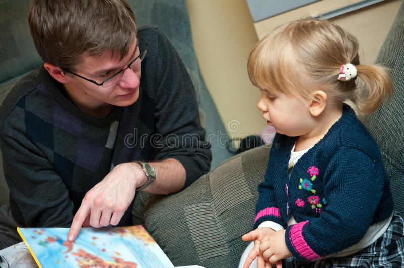Read fairytale. Baby girl with her older brother or uncle about to read her a book fairytale, pointing to the page of the colorful book royalty free stock photo