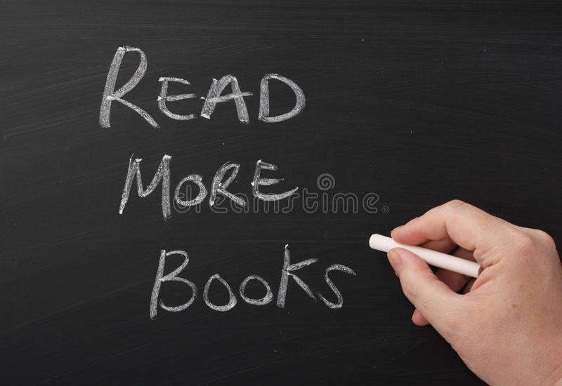 Read More Books. A hand writing Read More Books in chalk on a used blackboard. Reading is the key to success in education, general knowledge and literacy and stock photos