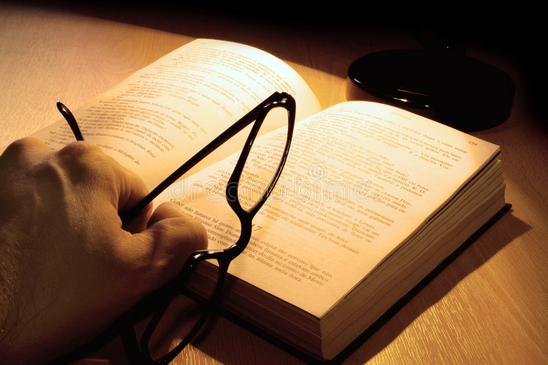 Reader. Holding glasses over a book stock image
