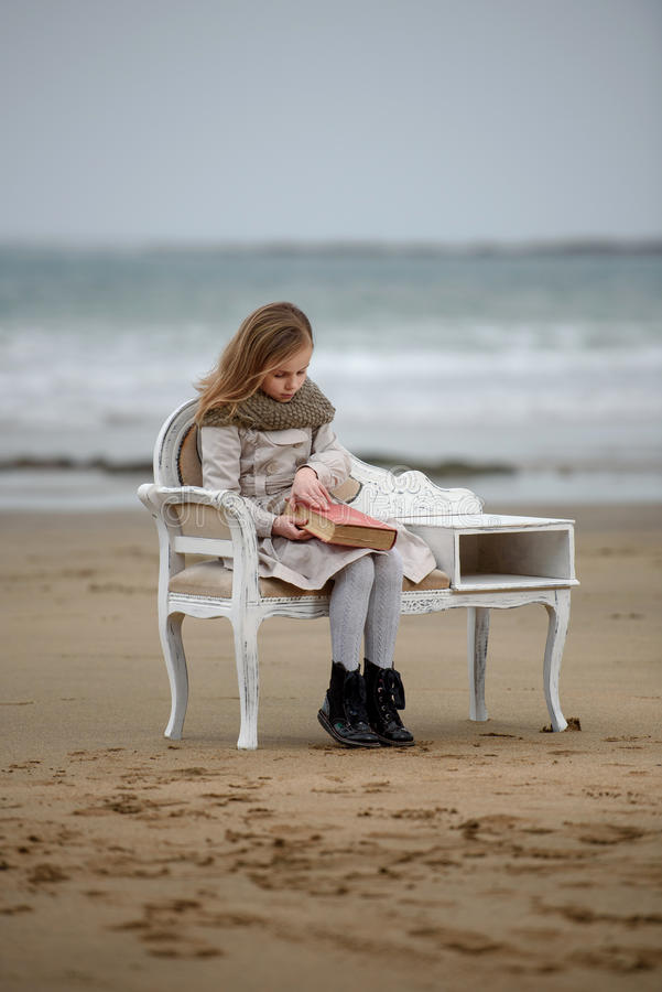 Reader. Little girl reading a book at the beach royalty free stock photo