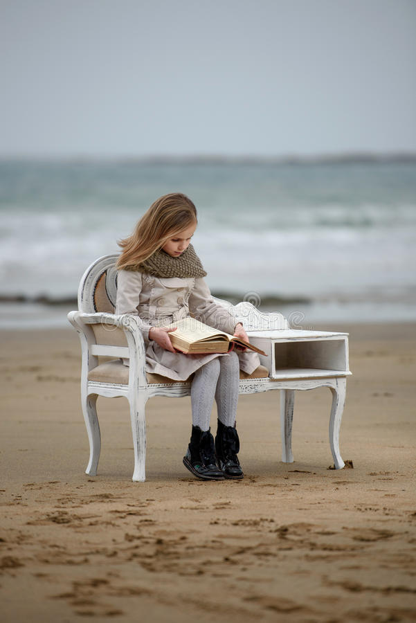 Reader. Little girl reading a book at the beach stock photo