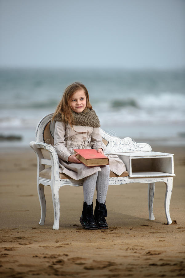 Reader. Little girl reading a book at the beach stock images