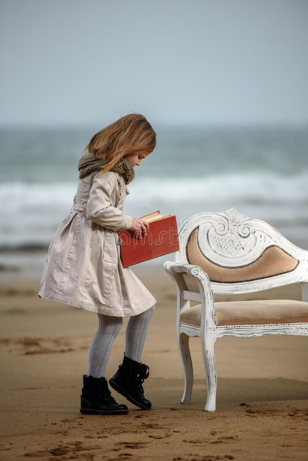 Reader. Little girl reading a book at the beach royalty free stock photos