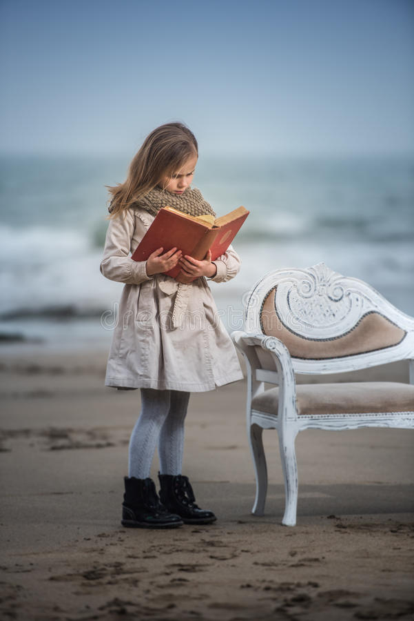 Reader. Little girl reading a book at the beach royalty free stock photography