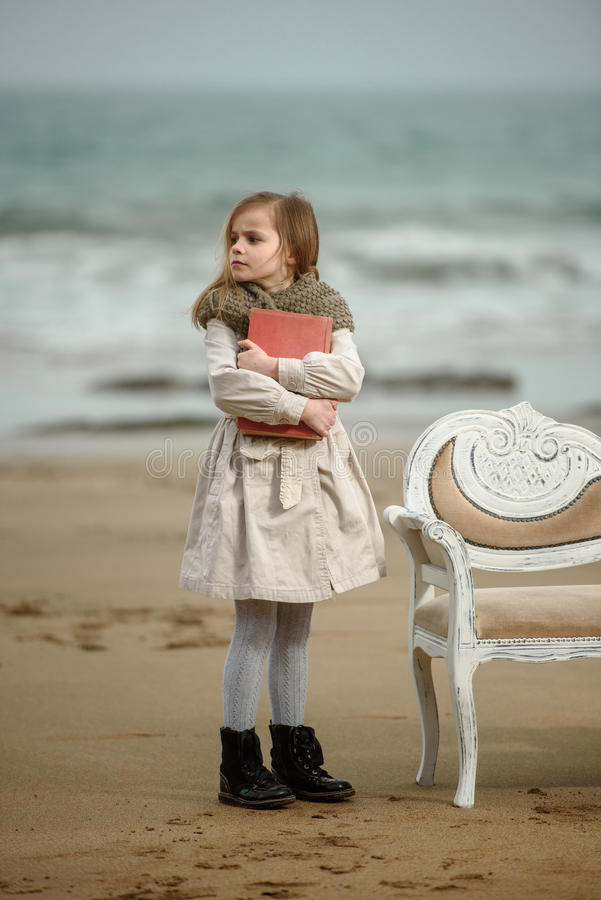 Reader. Little girl reading a book at the beach royalty free stock images