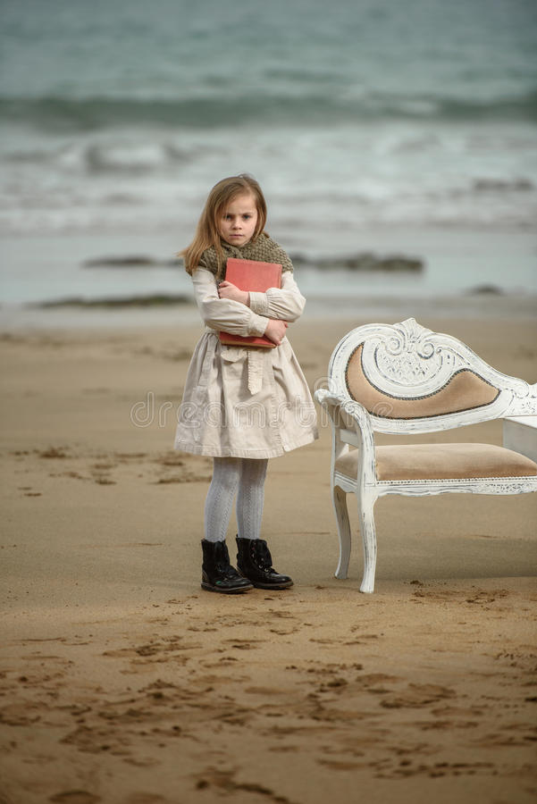 Reader. Little girl reading a book at the beach stock image
