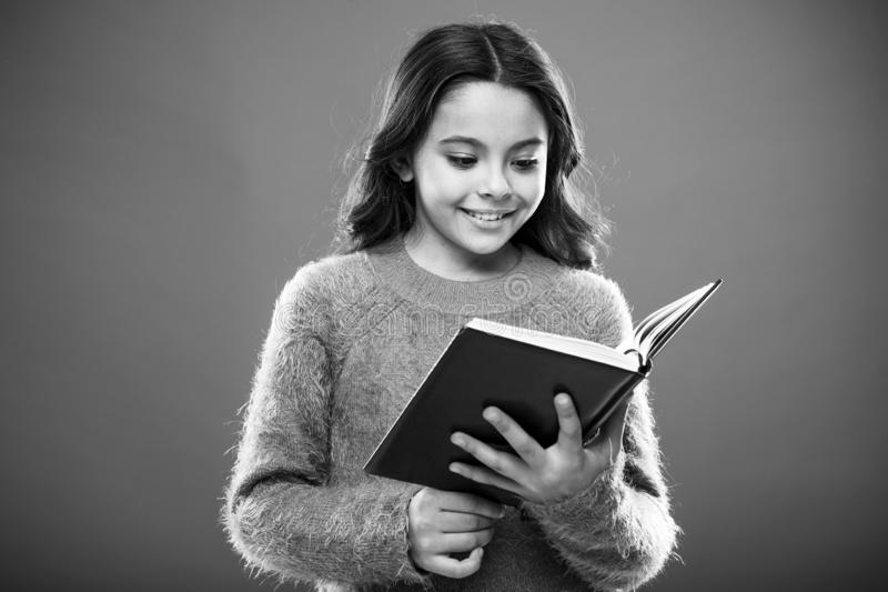 Reading activities for kids. Girl hold book read story over orange background. Child enjoy reading book. Book store royalty free stock photography