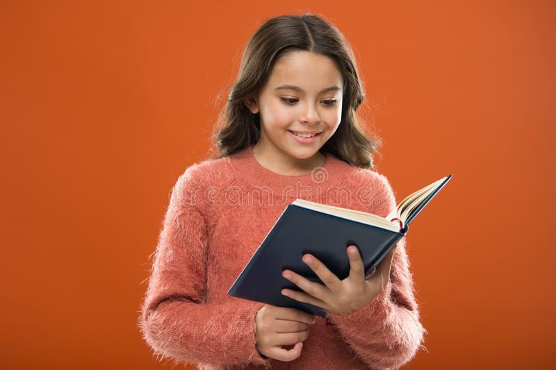 Reading activities for kids. Girl hold book read story over orange background. Child enjoy reading book. Book store stock photography