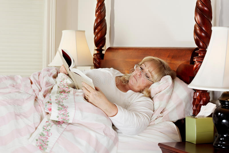Reading in bed. Mature woman reads a book while lying in bed stock images