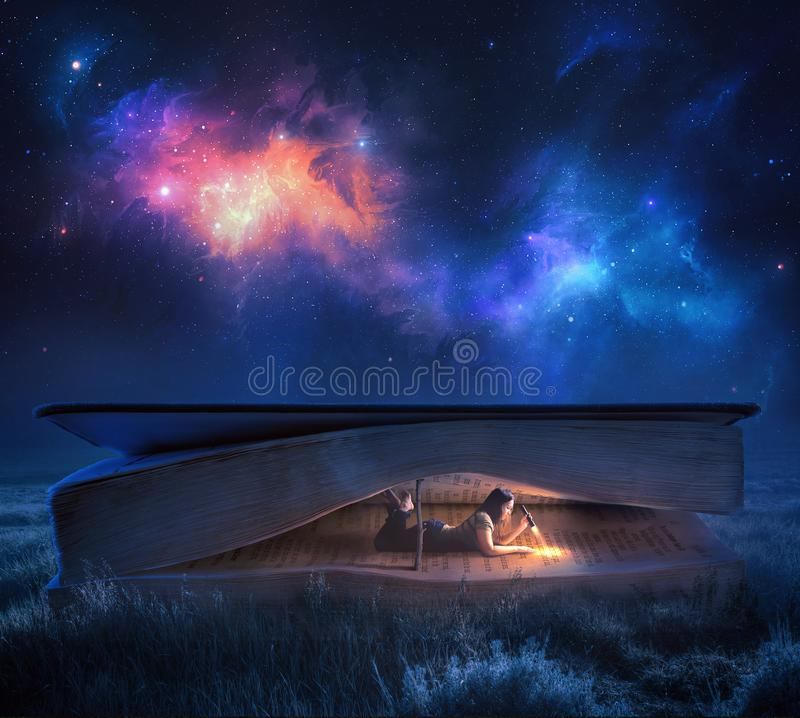 Reading a Bible at night. A woman reads a large Bible at night under the stars royalty free stock images