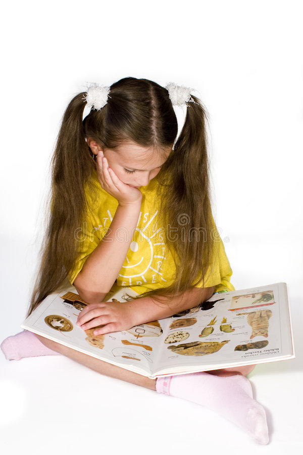 Reading book. Young girl reading a picture book royalty free stock images