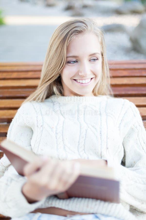 Reading a book. Attractive girl reading a book in the park stock photos