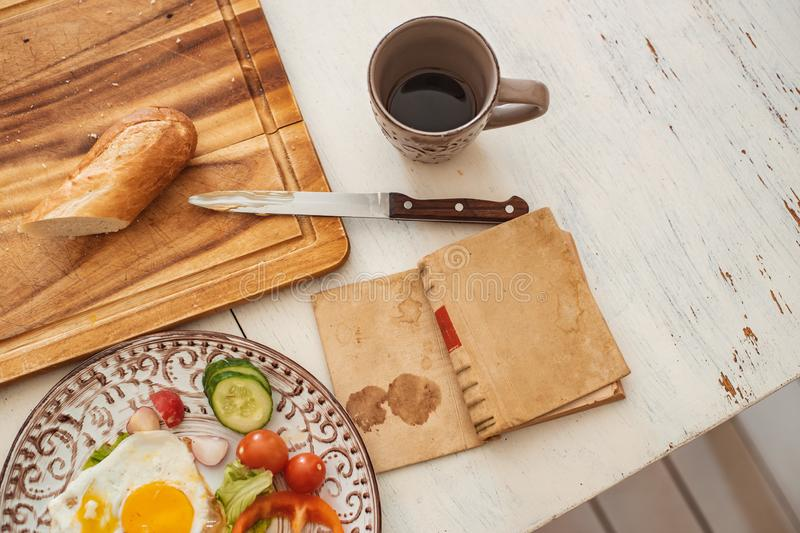 Reading a book at breakfast scrambled eggs, fresh vegetables knife and bread on a white rustic table royalty free stock photography