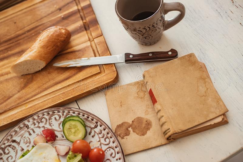 Reading a book at breakfast scrambled eggs, fresh vegetables knife and bread on a white rustic table royalty free stock photos