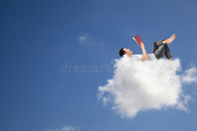 Reading Book On The Cloud Stock Photo