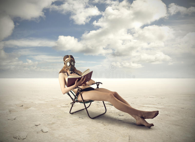 Reading a book in the desert royalty free stock photography