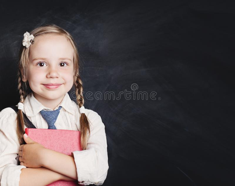 Reading book and education concept. Smiling child girl in school. Uniform on chalkboard background. Back to school royalty free stock photography