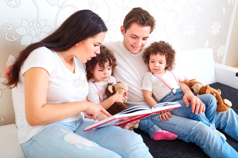 Reading a book with your family. A happy family. Children Twins. Sisters with Mom and Dad on the couch reading a book together. Training and education of royalty free stock photos