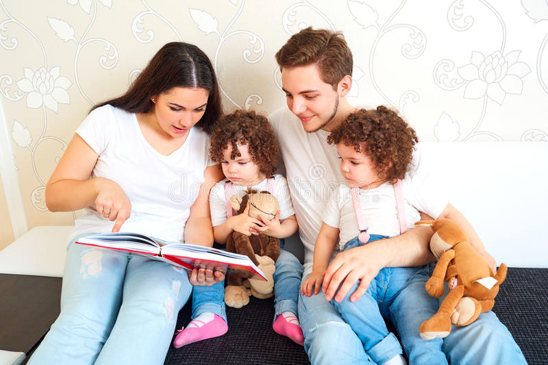 Reading a book with your family. A happy family. Children Twins. Sisters with Mom and Dad on the couch reading a book together. Training and education of stock photography