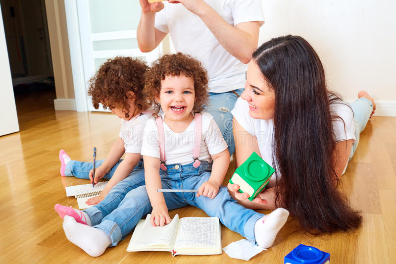 Reading a book with your family. A happy family. Children Twins. Sisters with Mom and Dad on the couch reading a book together. Training and education of stock photos