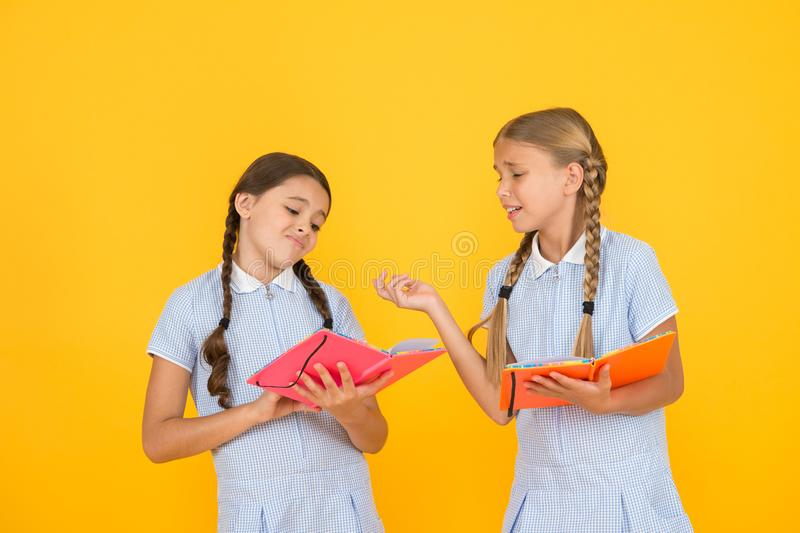 Reading books. Reading and retelling. Small children holding books yellow background. Sincere interest. Little girls stock photo