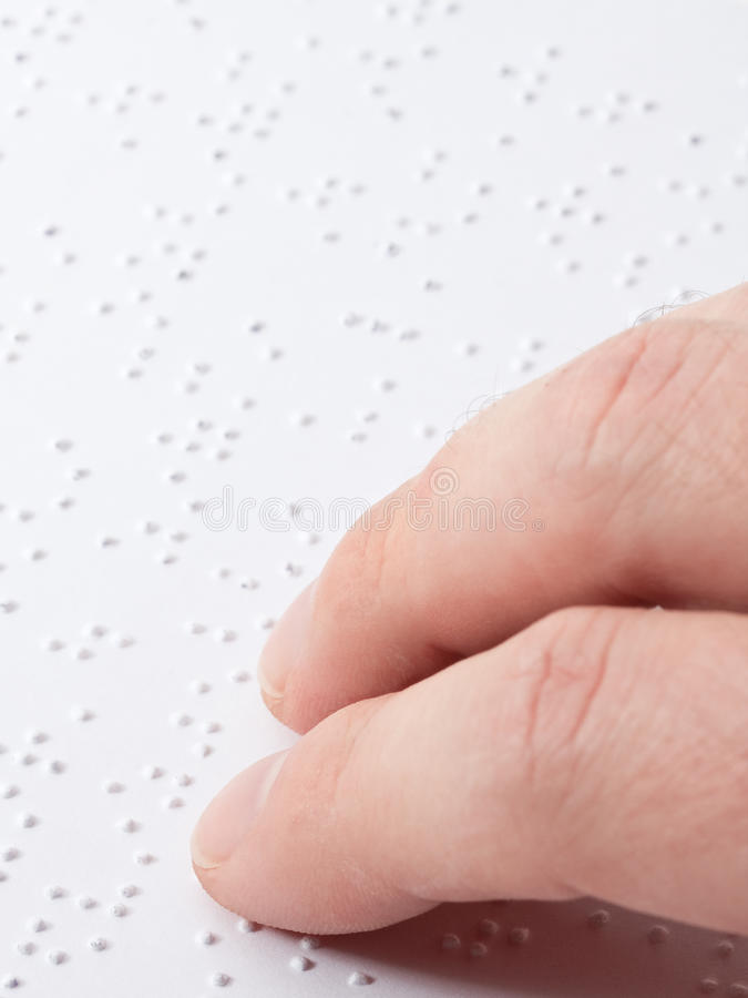 Reading braille. Close up of male hand reading braille text stock photo