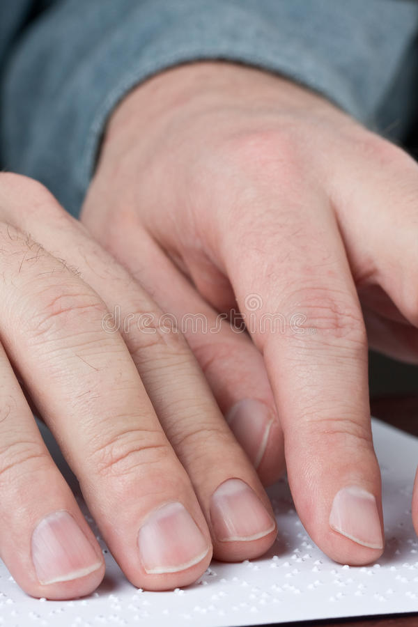 Reading braille. Close up of male hands reading braille text stock photos