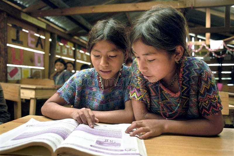 Reading class for native Guatemalan Indian girls. Guatemala, department Alto Verapaz, village Parachoch: in the mountains around Coban group portrait of Poqomchi stock images