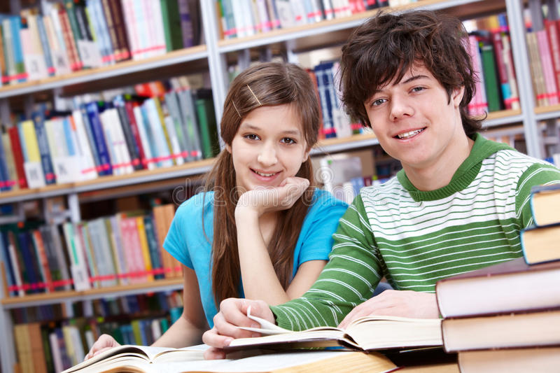 Reading classmates. Portrait of teenage girl and her classmate looking at camera in library royalty free stock photography