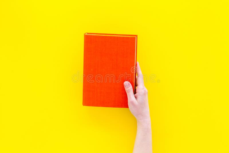 Reading concept. Reading as hobby. New knowledge. Hands take hardback book with empty cover on yellow background top. View stock photography
