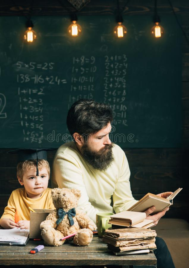 Reading concept. Teacher reading book to school boy. Little child listen to man reading book in class. Keep reading stock images