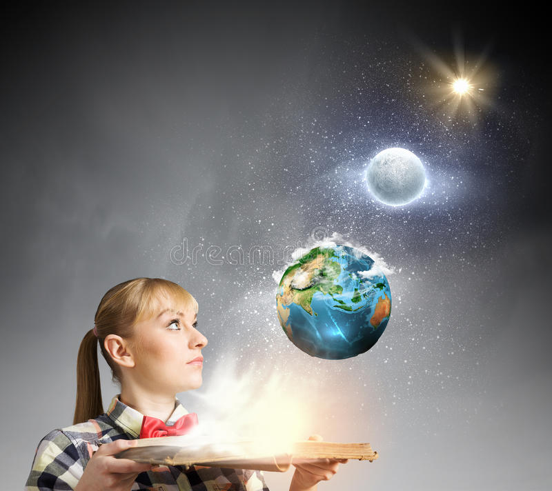 Reading concept. Woman in casual wear holding opened book in hands. elements of this image are furnished by NASA stock images