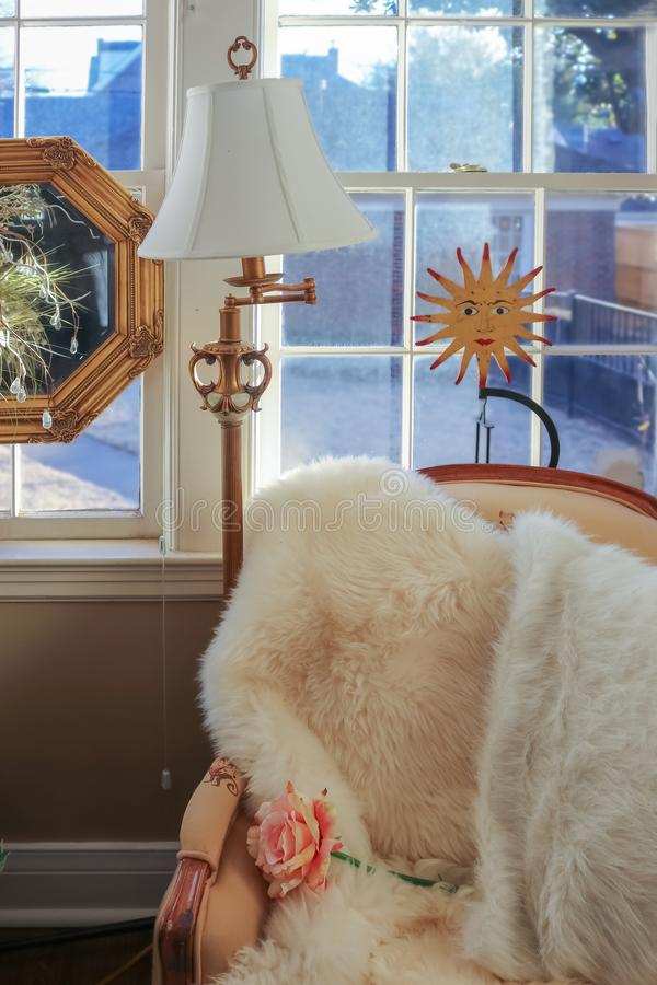 Reading corner - comfortable chair with fur throw and a rose by windows and lamp with happy sun and mirrow decor behind and stock image