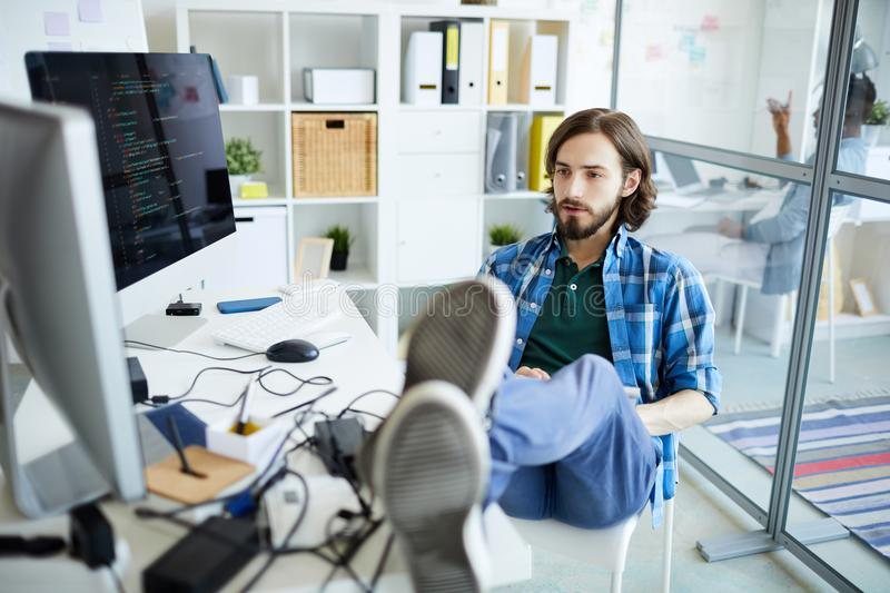 Reading data on screen. Young relaxed it-manager sitting on chair with his legs on desk and looking at computer screen in front of him royalty free stock image