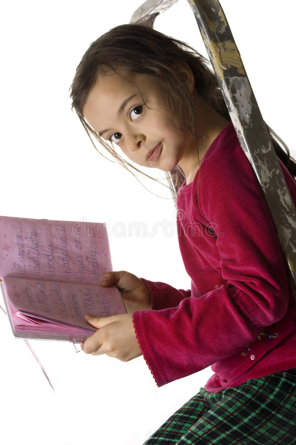 Reading diary. Little girl reading her diary on the ladder royalty free stock images