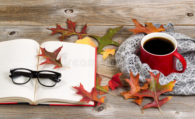 Reading and drinking dark coffee for the autumn season. Coffee, autumn leaves, book, reading glasses and grey scarf on rustic wood royalty free stock photos