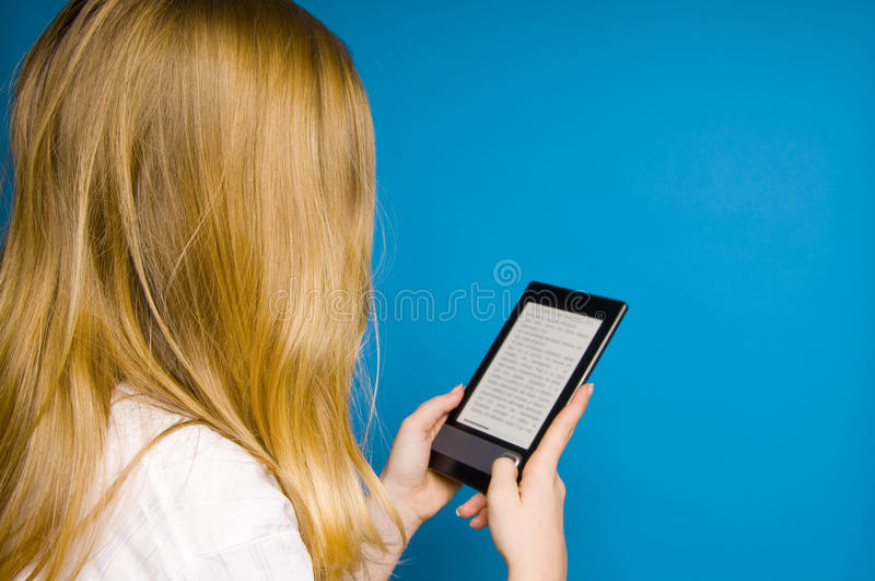 Reading ebook. Blond girl reading electronic books on an ebook reader device stock image