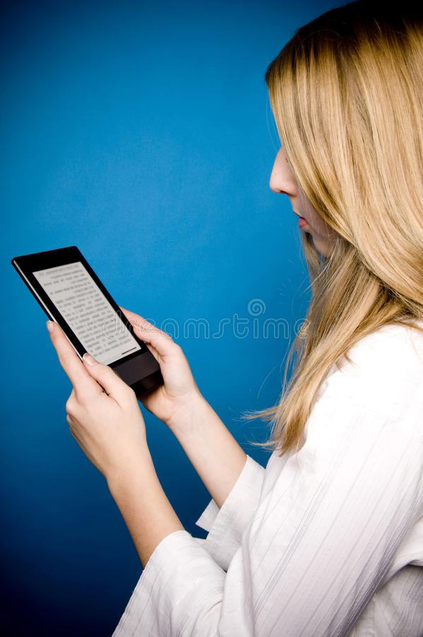 Reading ebook. Blond girl reading electronic books on an ebook reader device stock photography